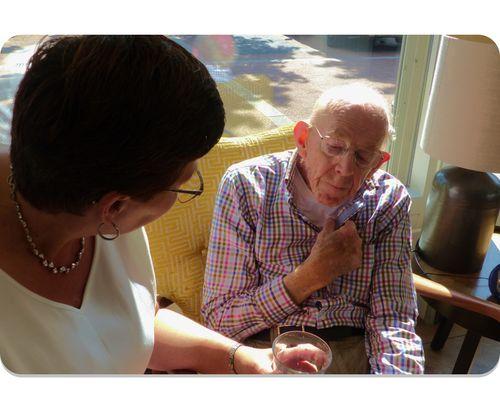 Een vrouwelijke Buddie die in gesprek is met een man van seniore leeftijd. Thuishulp en een luisterend oor in Noordwijk, Lisse, Katwijk, Valkenburg en Rijnsburg - Herberg Thuis
