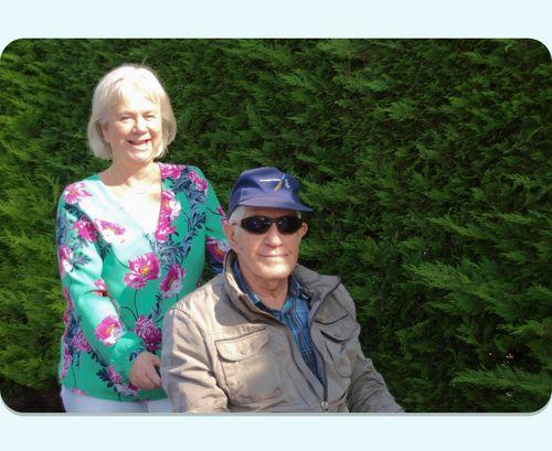 Een glimlachende Buddie van Herberg Thuis met een man in een rolstoel aan het wandelen in Valkenburg (Z-H)